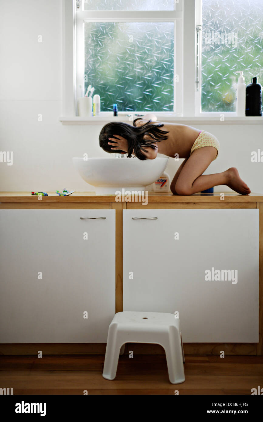Five year old girl climbs up to bathroom sink to drink water from tap - Stock Image
