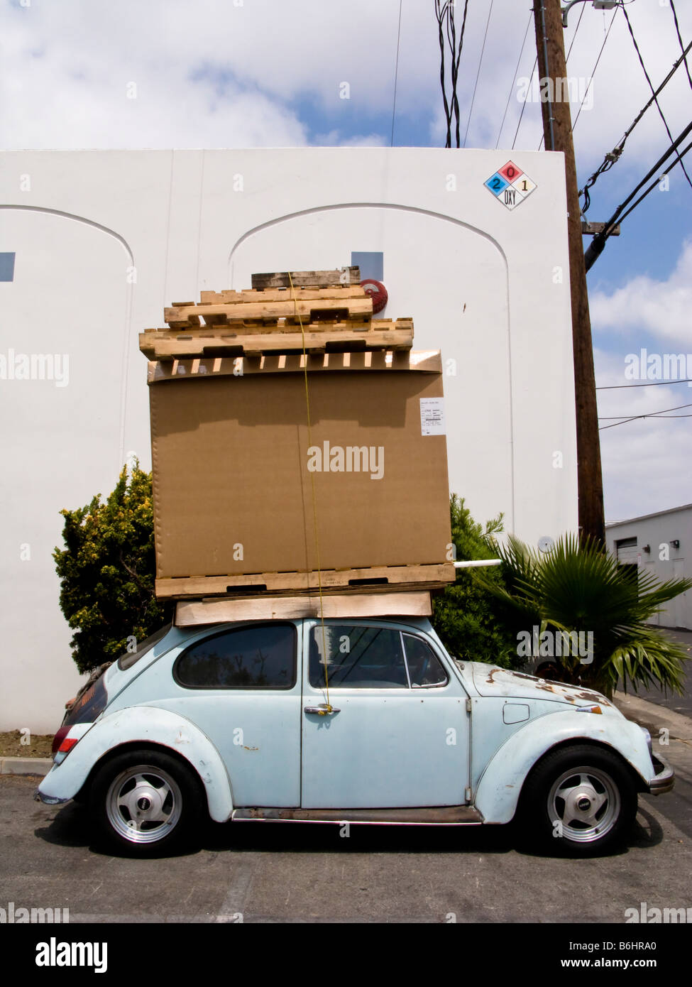 Cardboard boxes on top of roof of a VW beetle car - Stock Image