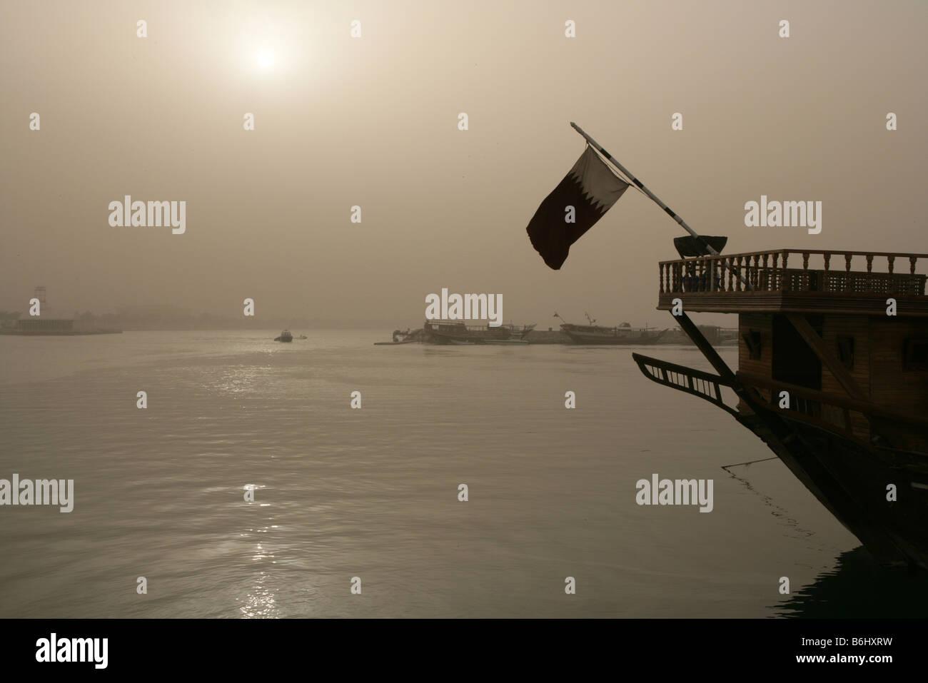 Qatari flag on traditional boat in sunlit haze, Doha Bay,Doha, Qatar, Middle East Stock Photo