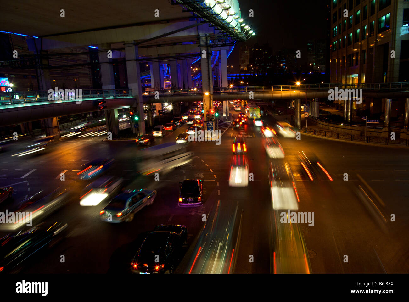 Downtown Shanghai traffic in chaotic motion blur rush hour gridlock at a big intersection under a freeway  pedestrian - Stock Image