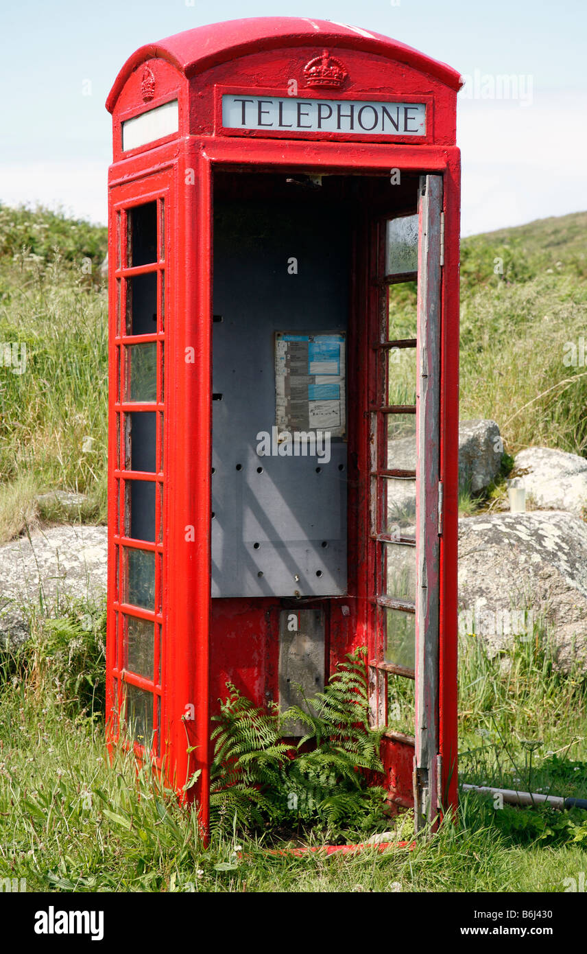 Disused British red telephone box kiosk with a missing door. - Stock Image