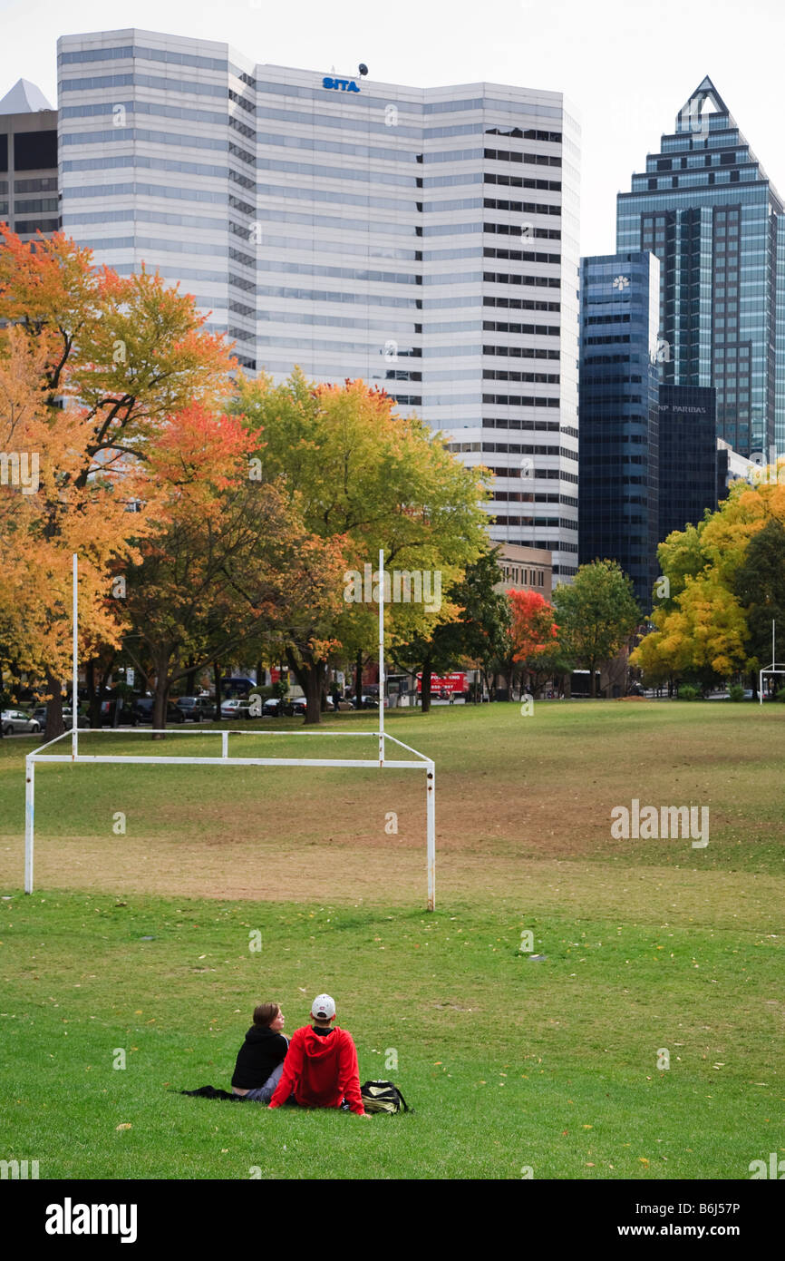 Students siting on grass of soccer field at McGill University Campus Montreal Quebec Canada - Stock Image