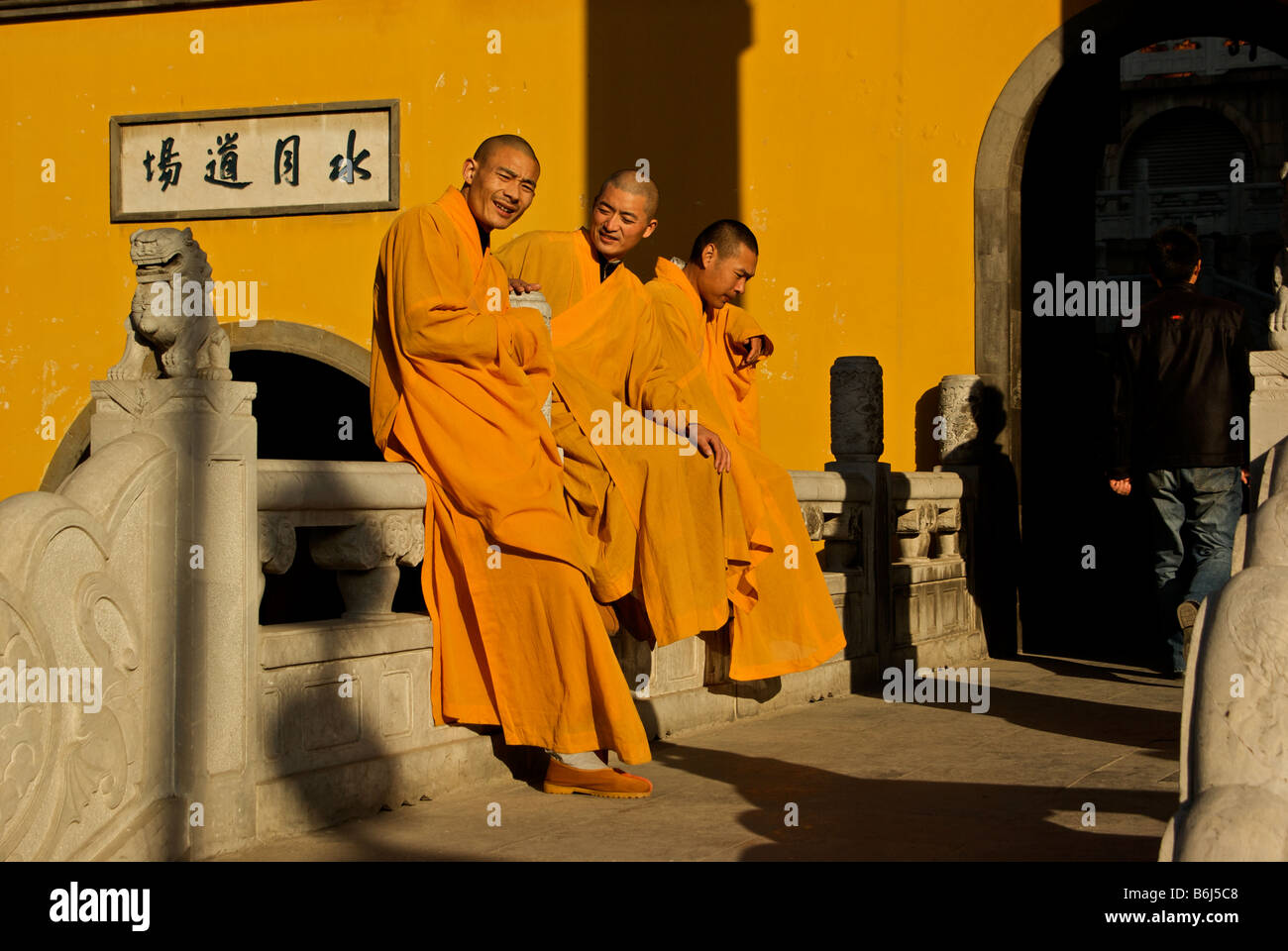 Three young orange robed monks leaning against sculpted stone wall entrance bridge to Tang dynasty Zhenjiang Buddhist - Stock Image