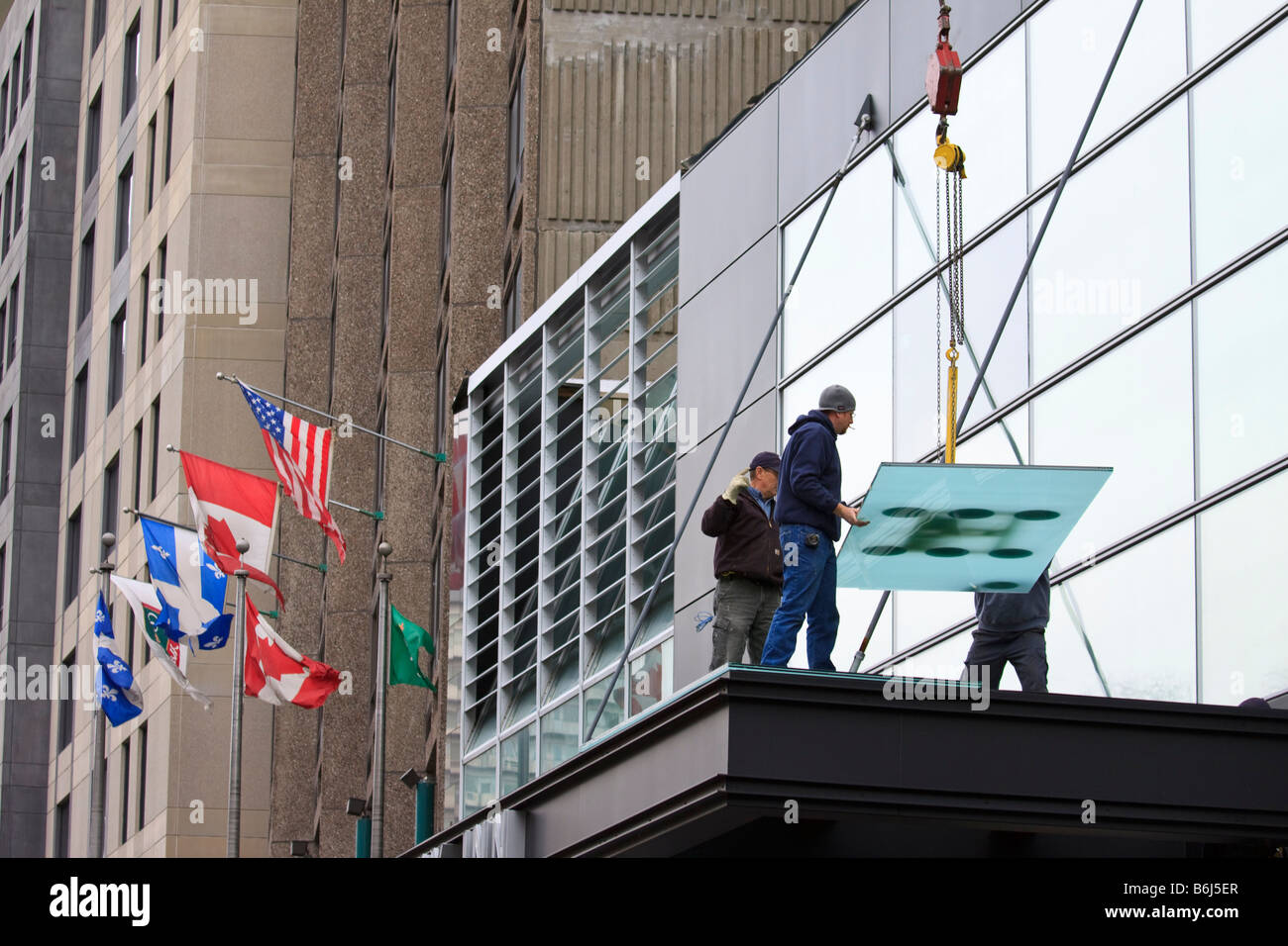 Workmen installing large glass panels in hotel Montreal Quebec Canada - Stock Image
