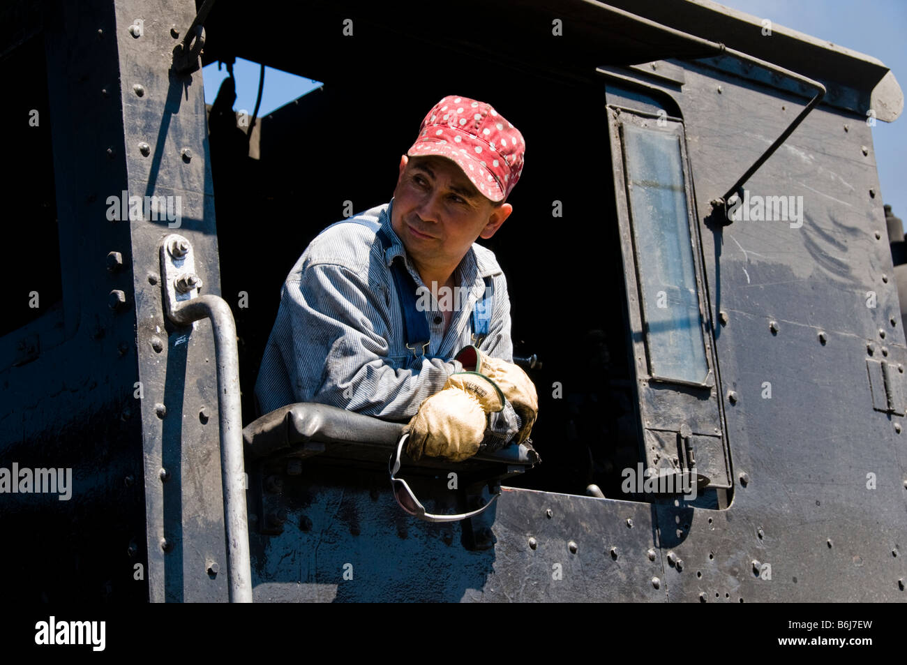Train engineer looking out of cab on Old fashioned vintage locomotive train engine - Stock Image