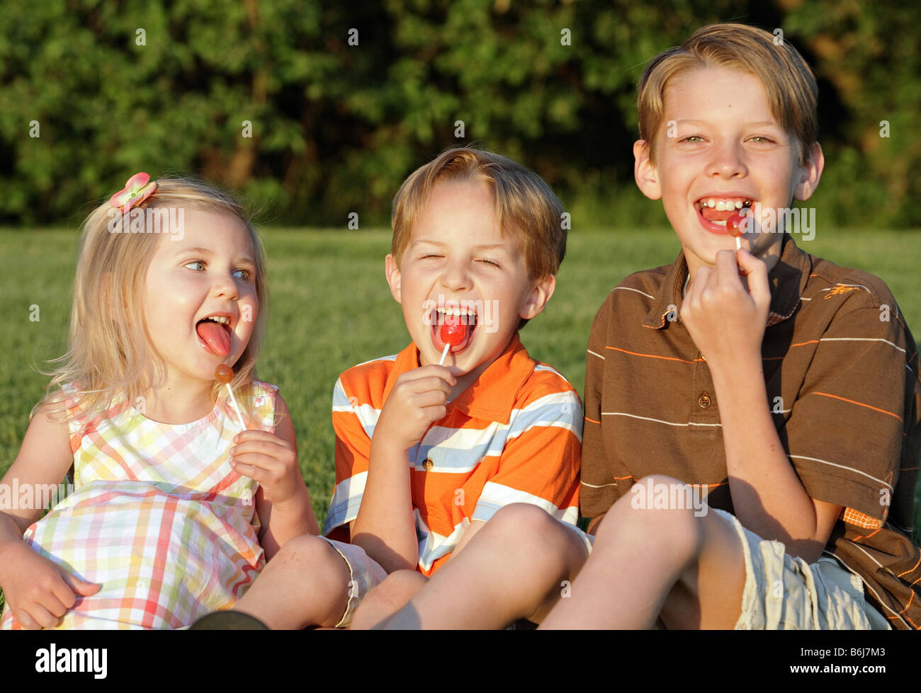 three children laughing and eating suckers outdoors - Stock Image