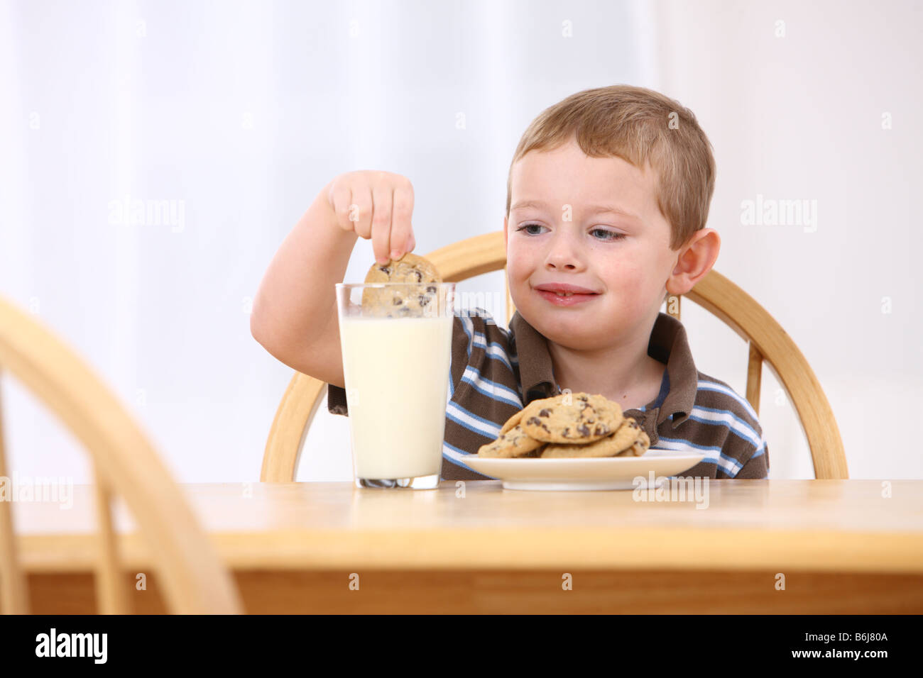 Young boy dipping cookie in glass of milk - Stock Image
