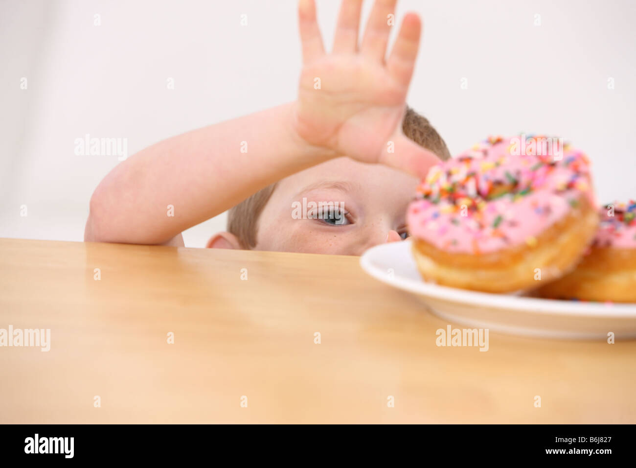 Young boy reaching for donuts on table - Stock Image