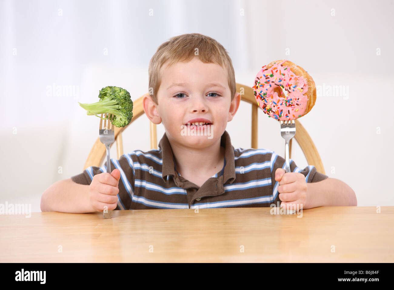 Young boy with donut and broccoli on forks - Stock Image