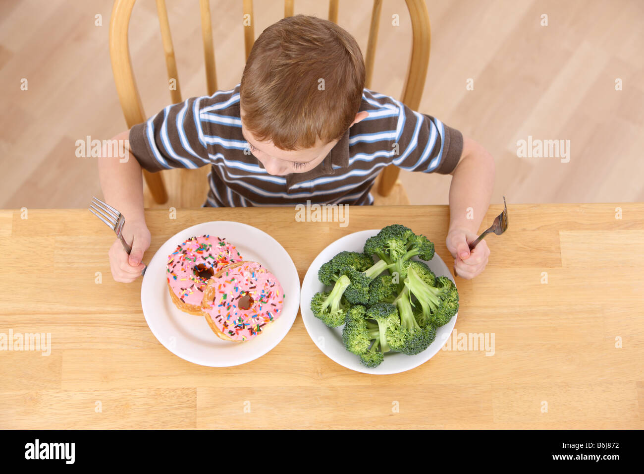 Young boy sitting at table with plates of broccoli and donuts - Stock Image