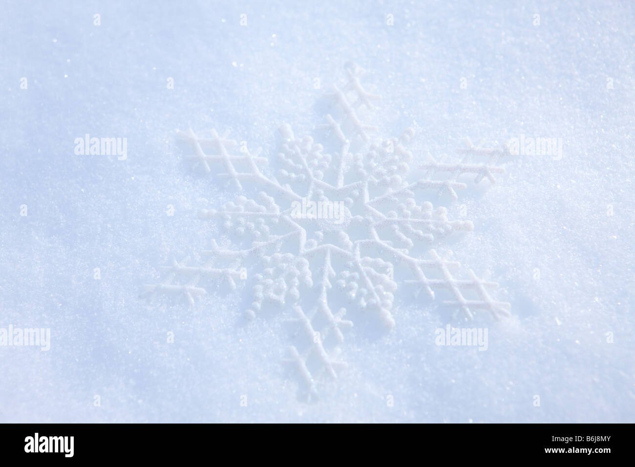 Snowflake ornament laying in fresh white winter snow - Stock Image
