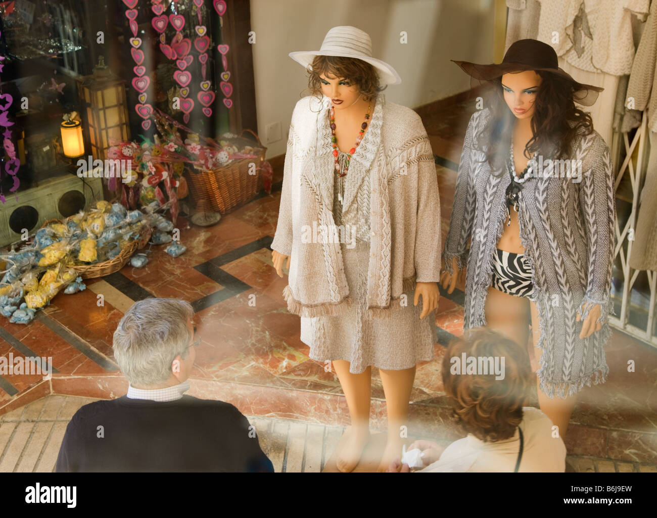 Man and woman looking at two realistic clothing dummies outside shop in Torremolinos Malaga Province Costa del Sol - Stock Image