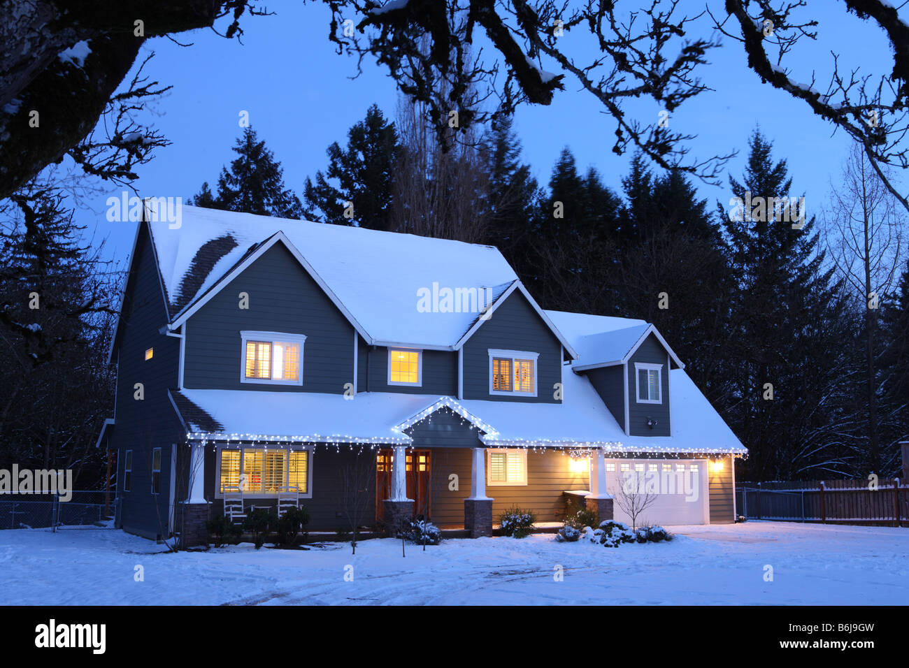winter home house at night with lights on and snow stock. Black Bedroom Furniture Sets. Home Design Ideas