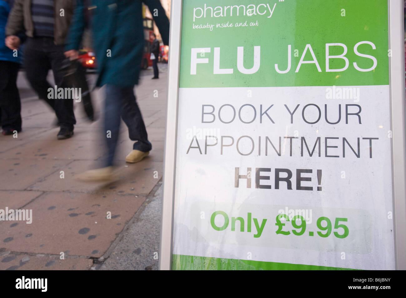 Advertising Flu jabs outside a chemist in London - Stock Image