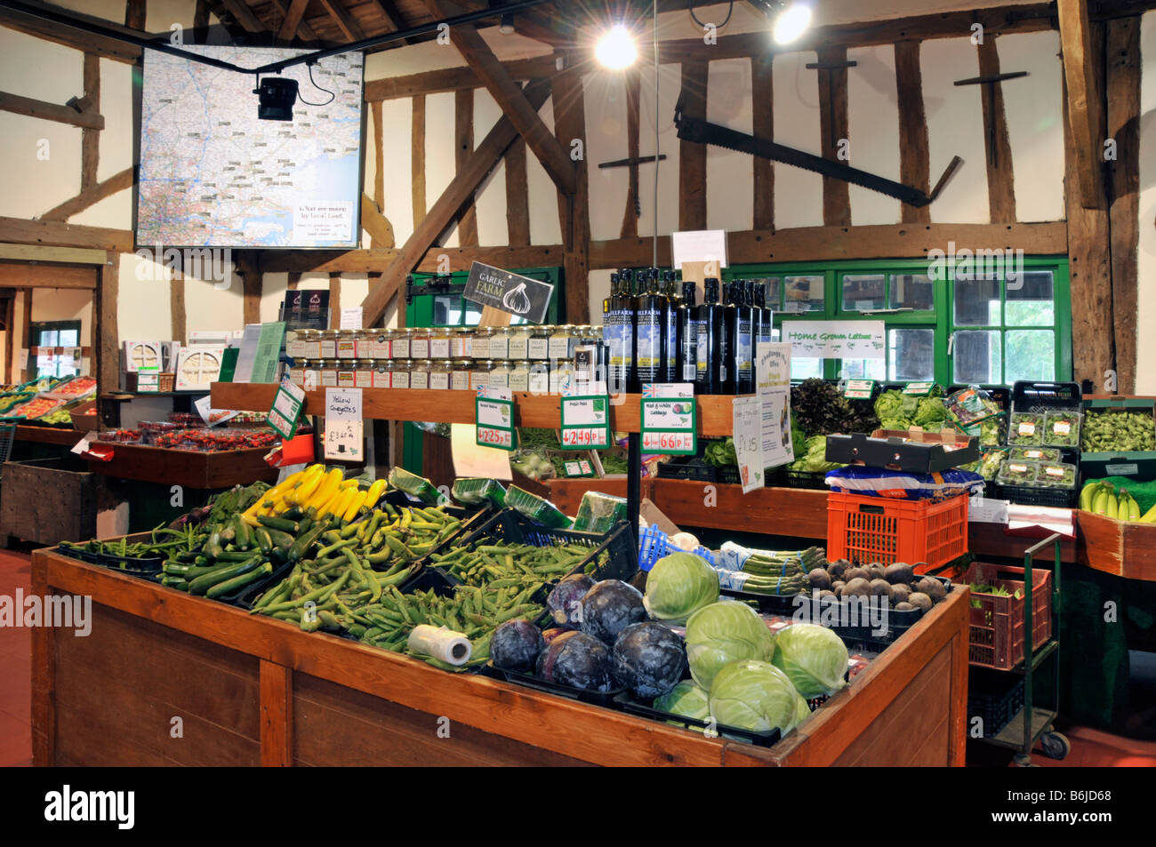 Interior of retail farm shop vegetables and general produce on display - Stock Image