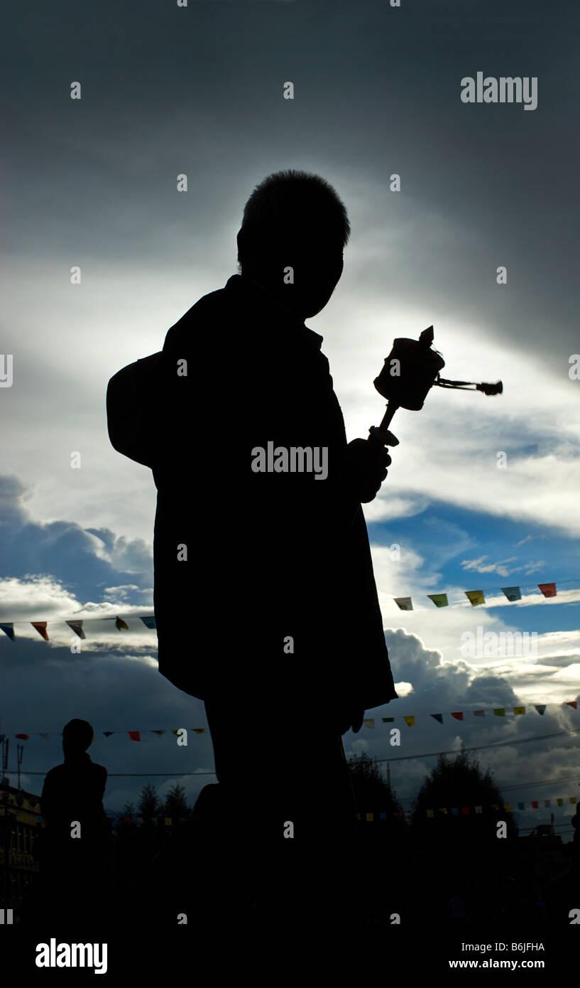 Silhouette of a Tibetan pilgrim spinning a prayerwheel as he makes a perumbulation of Jokhang monastery, Lhasa, - Stock Image