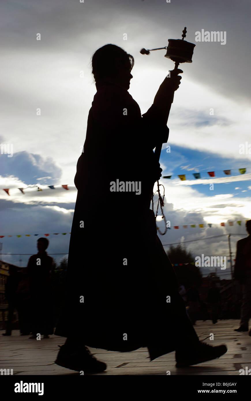 Silhouette of a Tibetan pilgrim spinning a prayerwheel as she makes a perumbulation of Jokhang monastery, Lhasa, - Stock Image