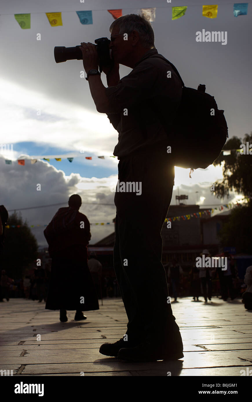 Silhouette of a photographer with a professional camera composing a photograph. Barkor Square, Tibet - Stock Image