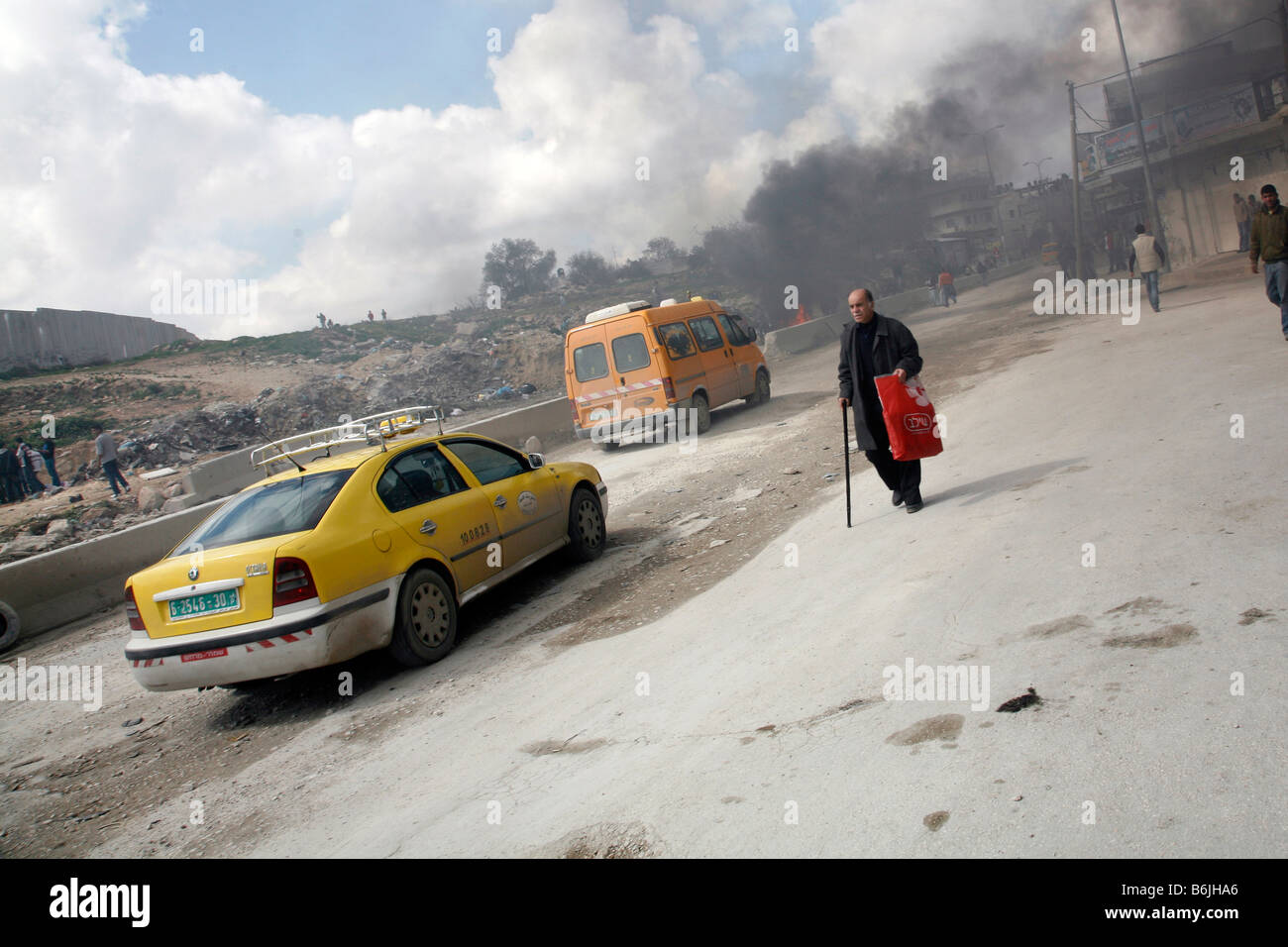 A Palestinian man walks past smoke from burning tyres during a protest in the West Bank. - Stock Image