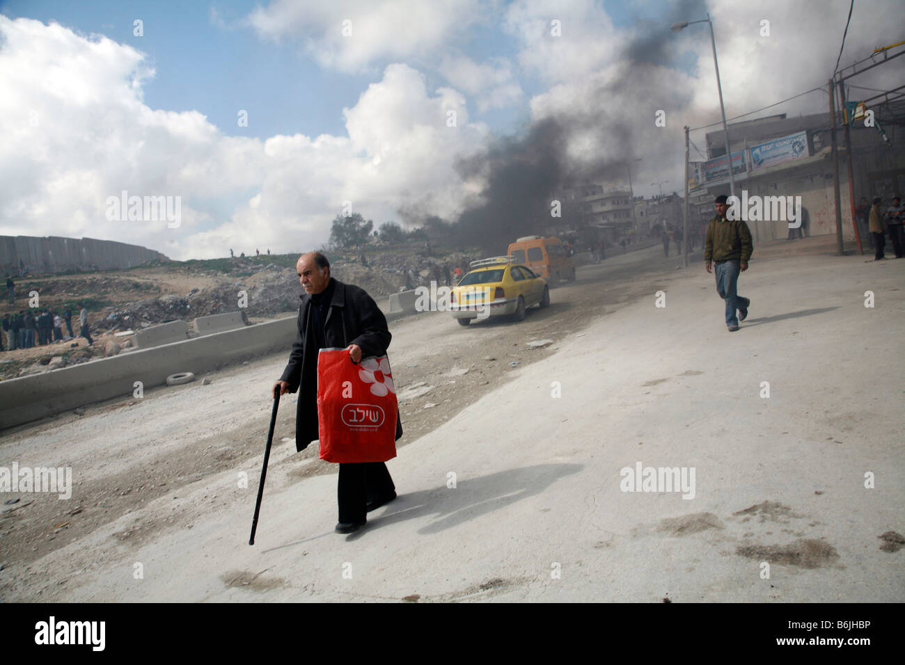 A Palestinian man walks past smoke from burning tyres near the Qalandiya checkpoint just north of Jerusalem in the - Stock Image