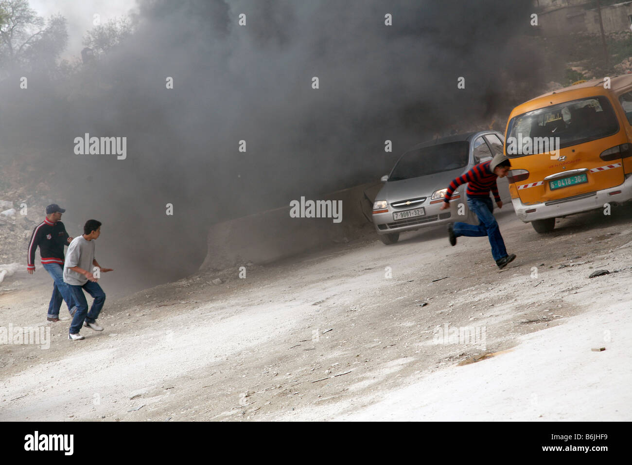 Palestinian youth running from Israeli soldiers during clashes in the West Bank. - Stock Image
