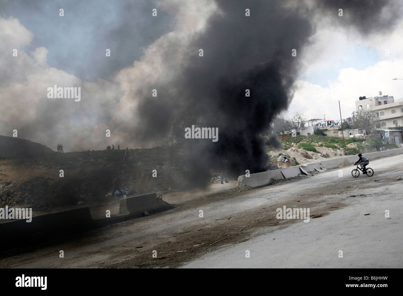 A Palestinian boy cycles through smoke from burning tyes during a protest in the West Bank. - Stock Image