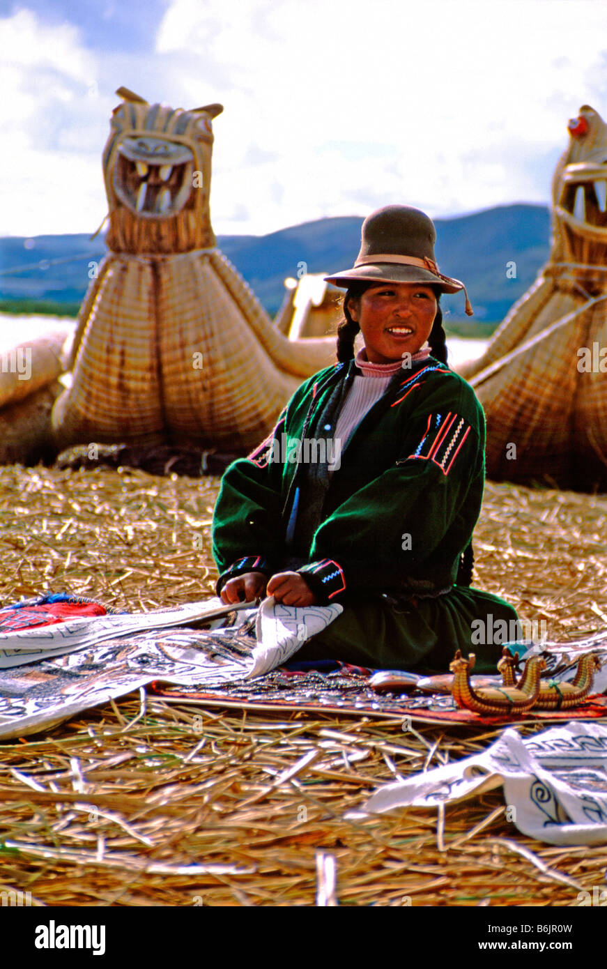 Uro indian woman in traditional attire selling handmade textiles. Typical reed dragon boats in distance. - Stock Image