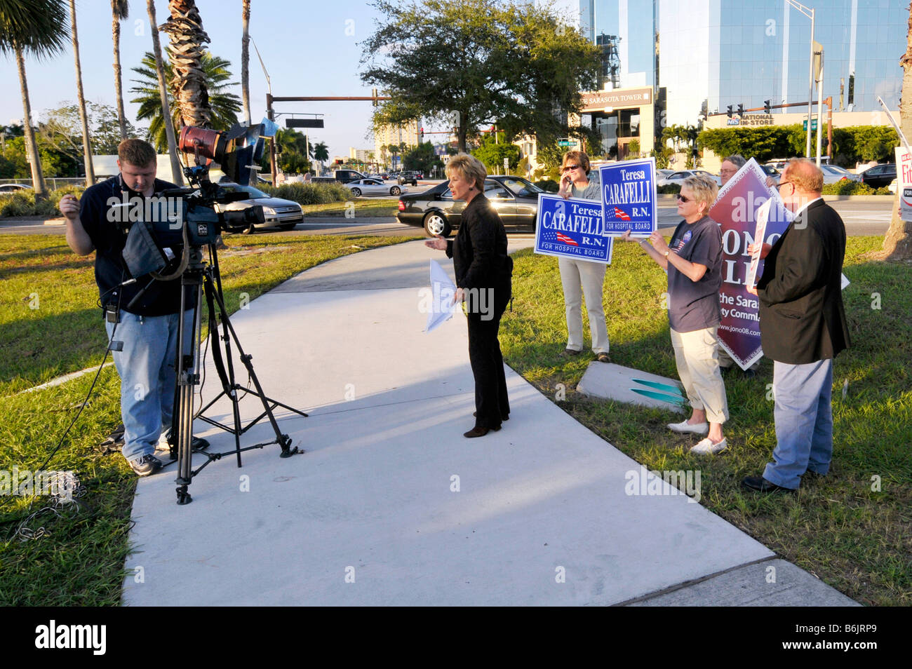 Female television news reporter interviews political supporters on busy street - Stock Image