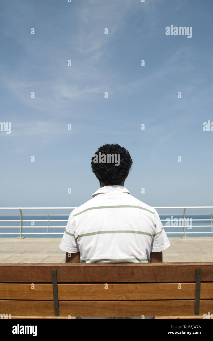 Man sitting on bench by the sea - Stock Image