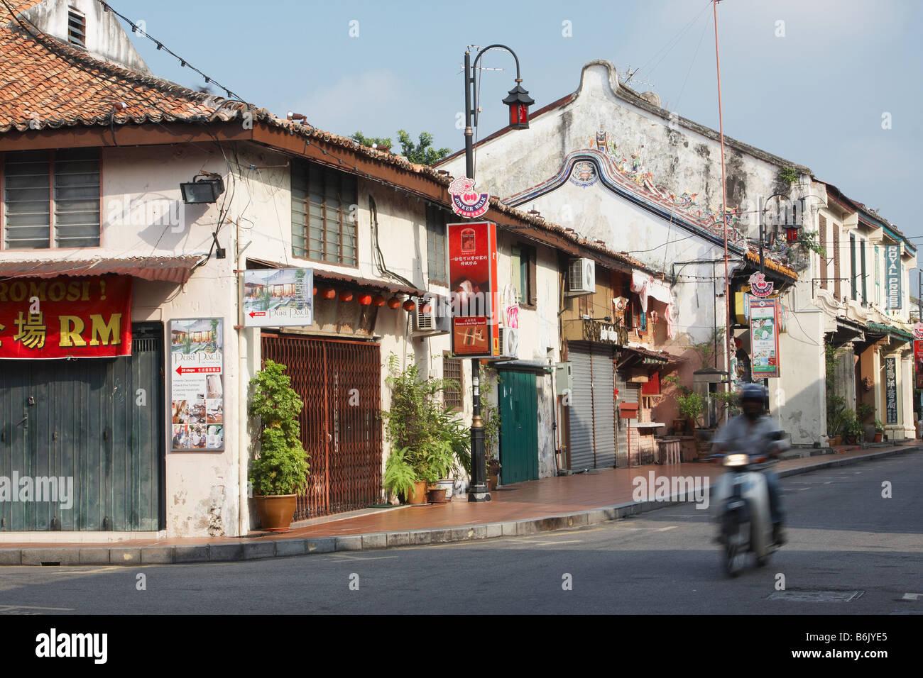 Motorcyclist Riding Along Street In Chinatown, Melaka - Stock Image