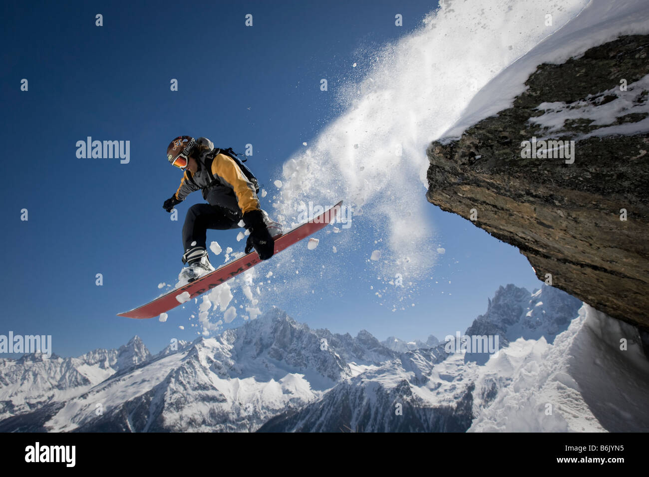 A snowboarder jumps off a rock at Le Brevent, Chamonix, France. Stock Photo