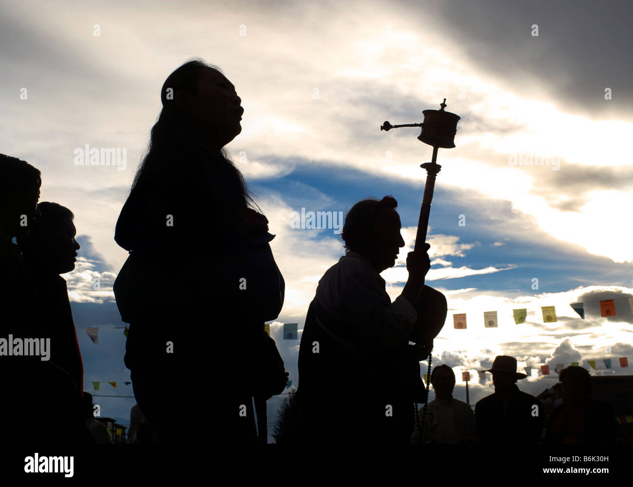 Silhouetted shape of a Tibetan pilgrims in Barkor Square, Lhasa, Tibet - Stock Image