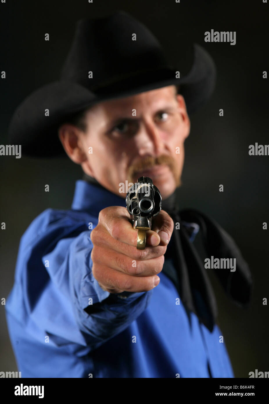 menacing cowboy aiming revolver gun at camera - Stock Image
