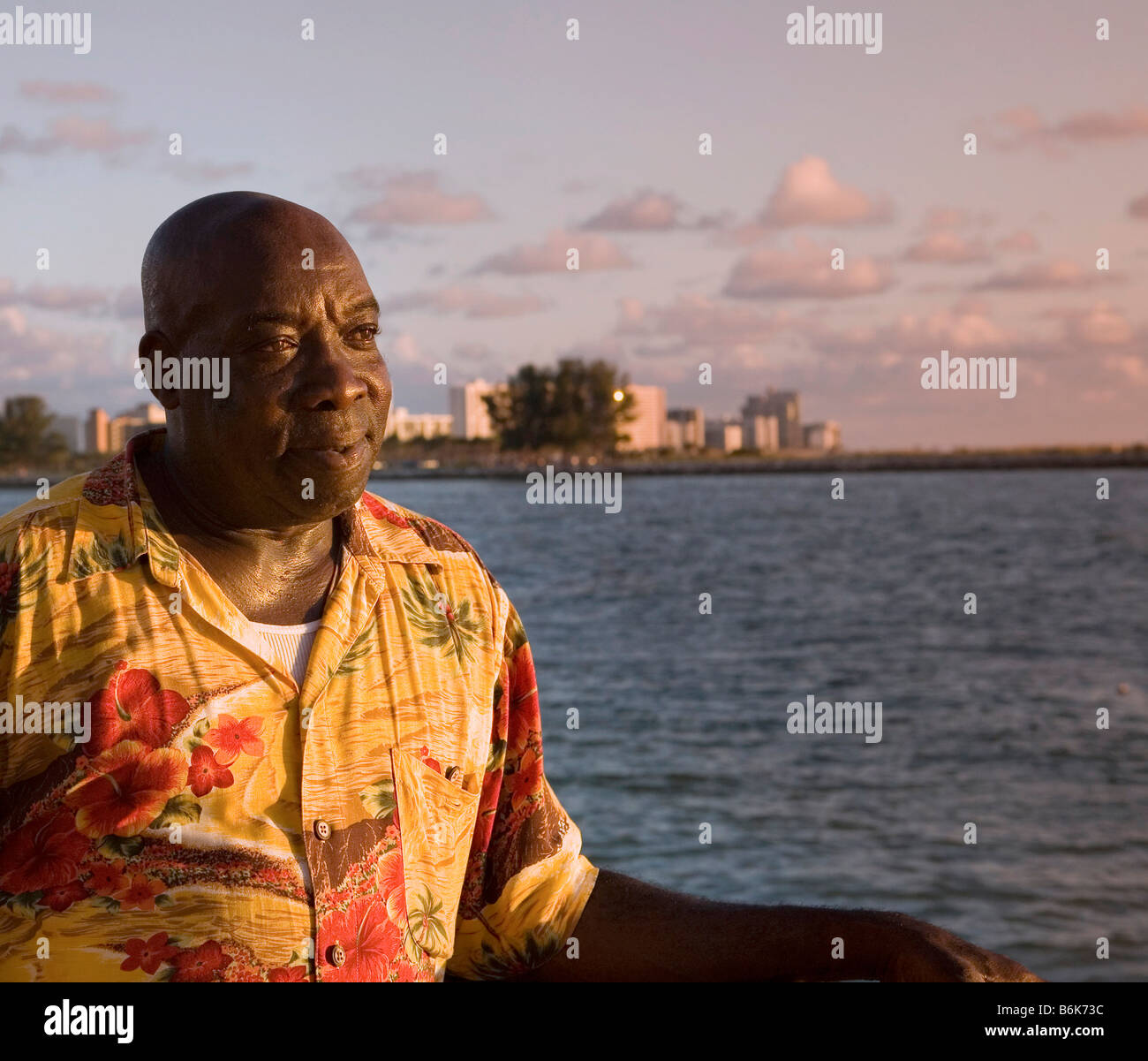 A caribbean man enjoying a tropical sunset over the water - Stock Image