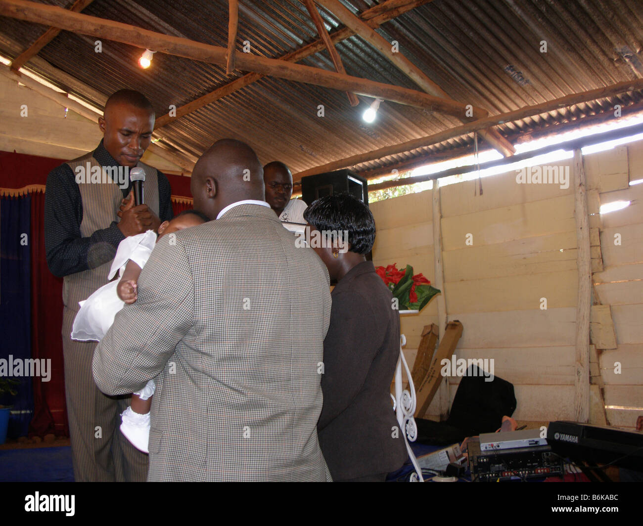 A born again pentecostal pastor blesses a young child in a makeshift church in Kampala, Uganda - Stock Image