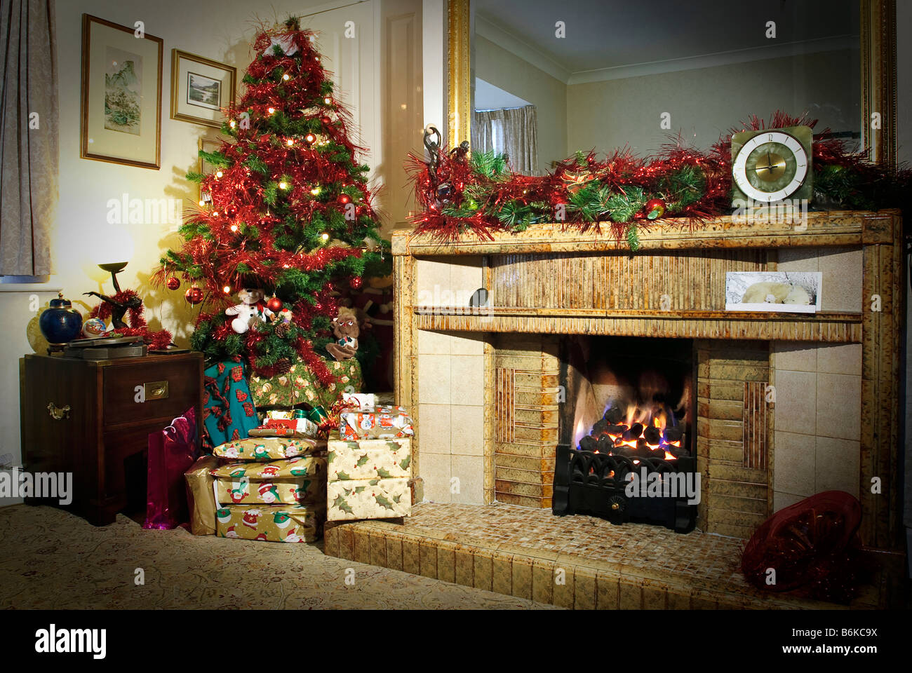 Christmas presents under the tree beside a warm fire - Stock Image