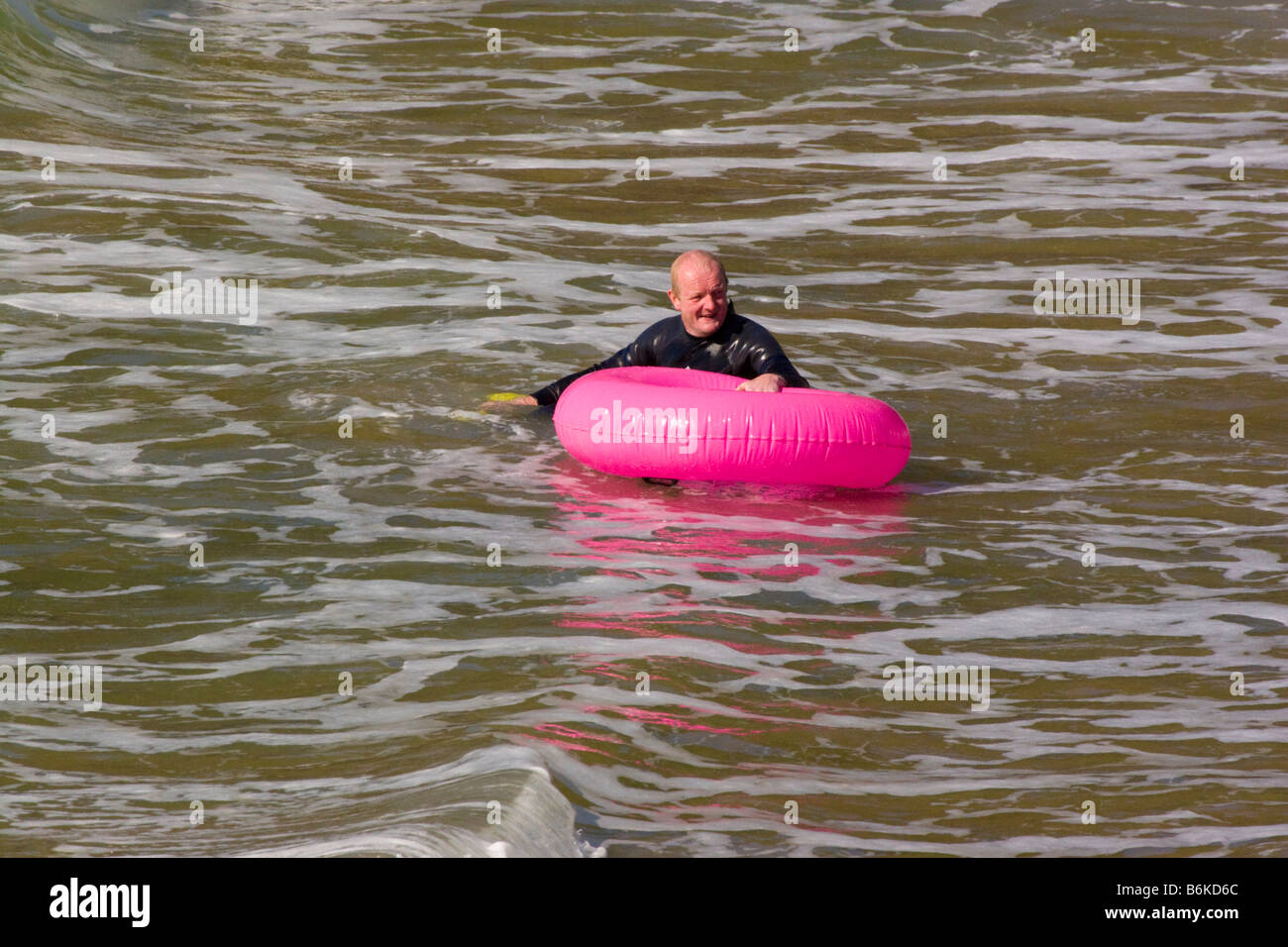 Llangrannog Beach Cardiganshire Cardigan bay Wales UK Man on giant pink rubber ring - Stock Image