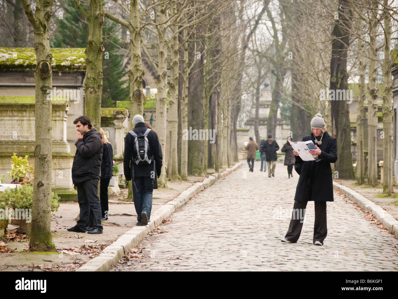 A man with a map that shows where all the famous people are buried at Pere Lachaise Cemetery  in Paris Stock Photo