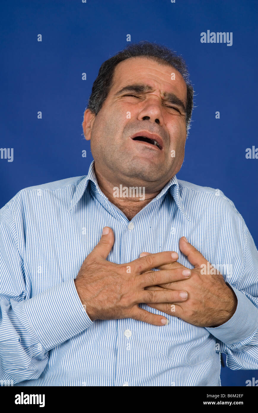 Man hands grabbing chest having a heart attack - Stock Image