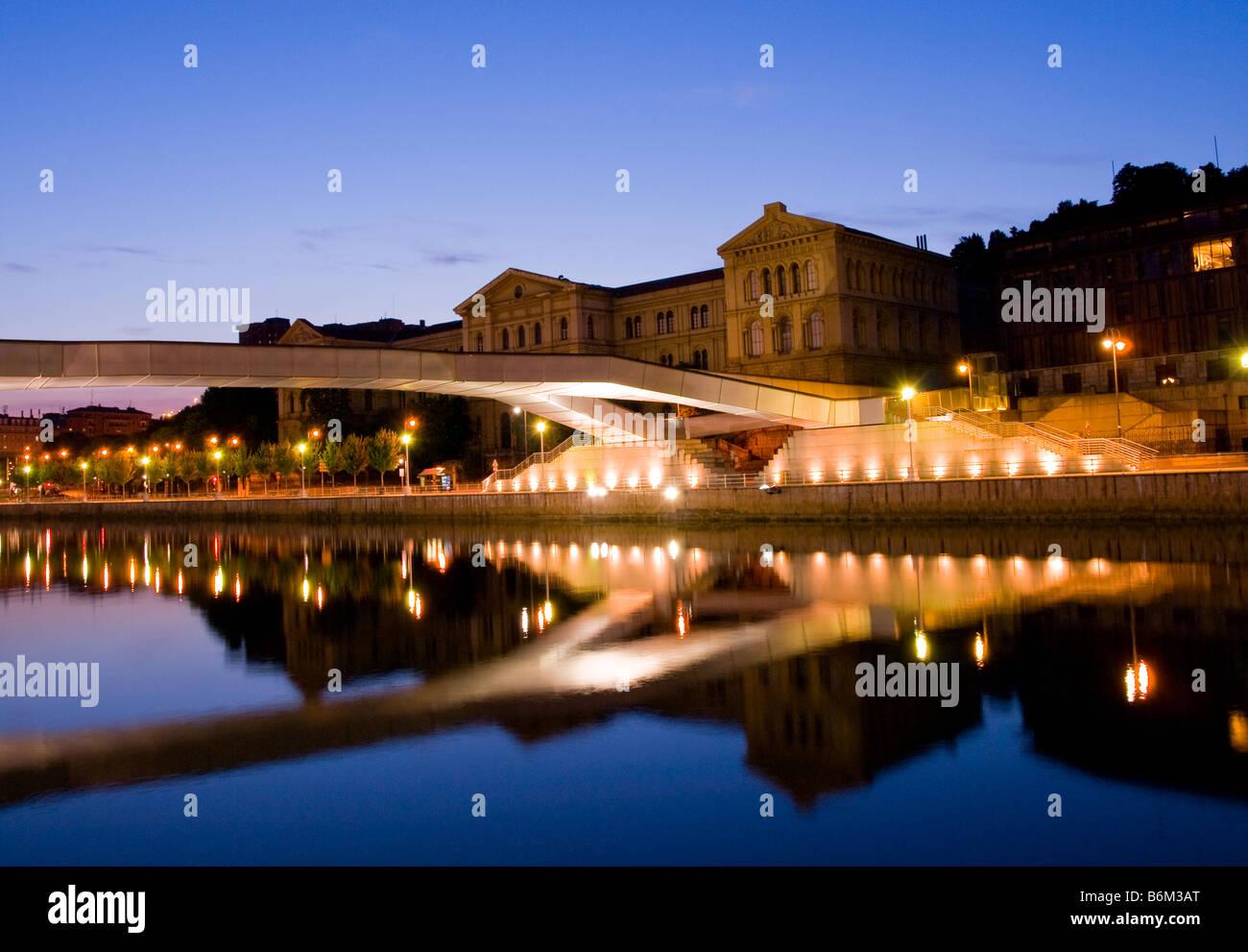 The Universidad de Deusto and the Puente Pedro Arrupe reflect on the Ría de Bilbao in Bilbao, Spain. - Stock Image