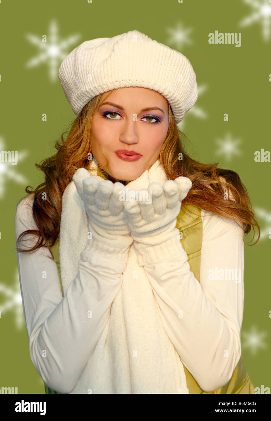 Pretty Blonde Woman Blowing Kisses Wearing Warm Winter Clothing - Stock Image