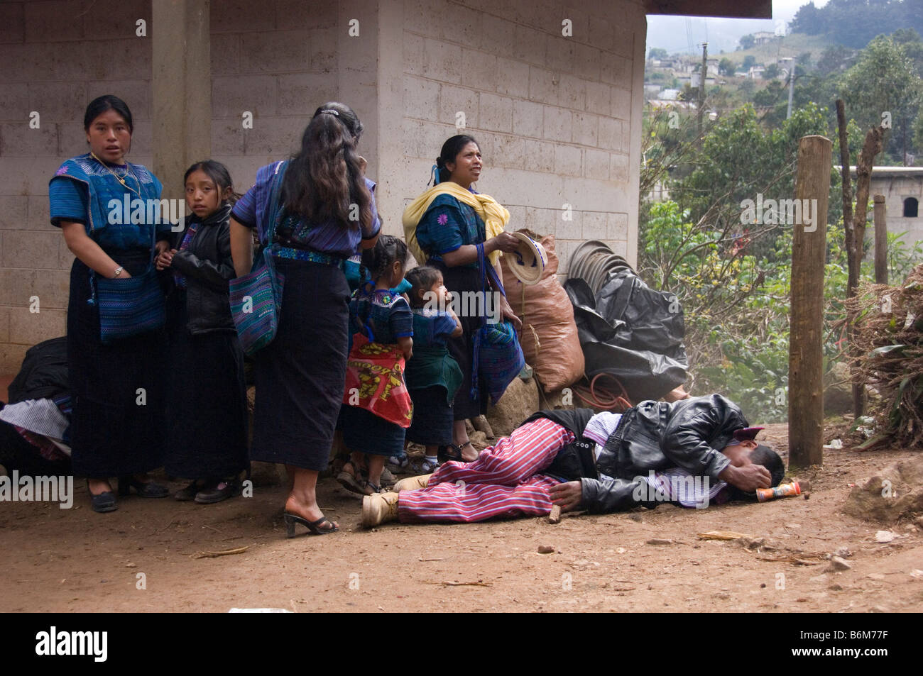 Boozer lays on the ground in front of his female family members.Annual festival (Oct 31-Nov 2) Todos Santos Cuchumatan,Guatemala - Stock Image