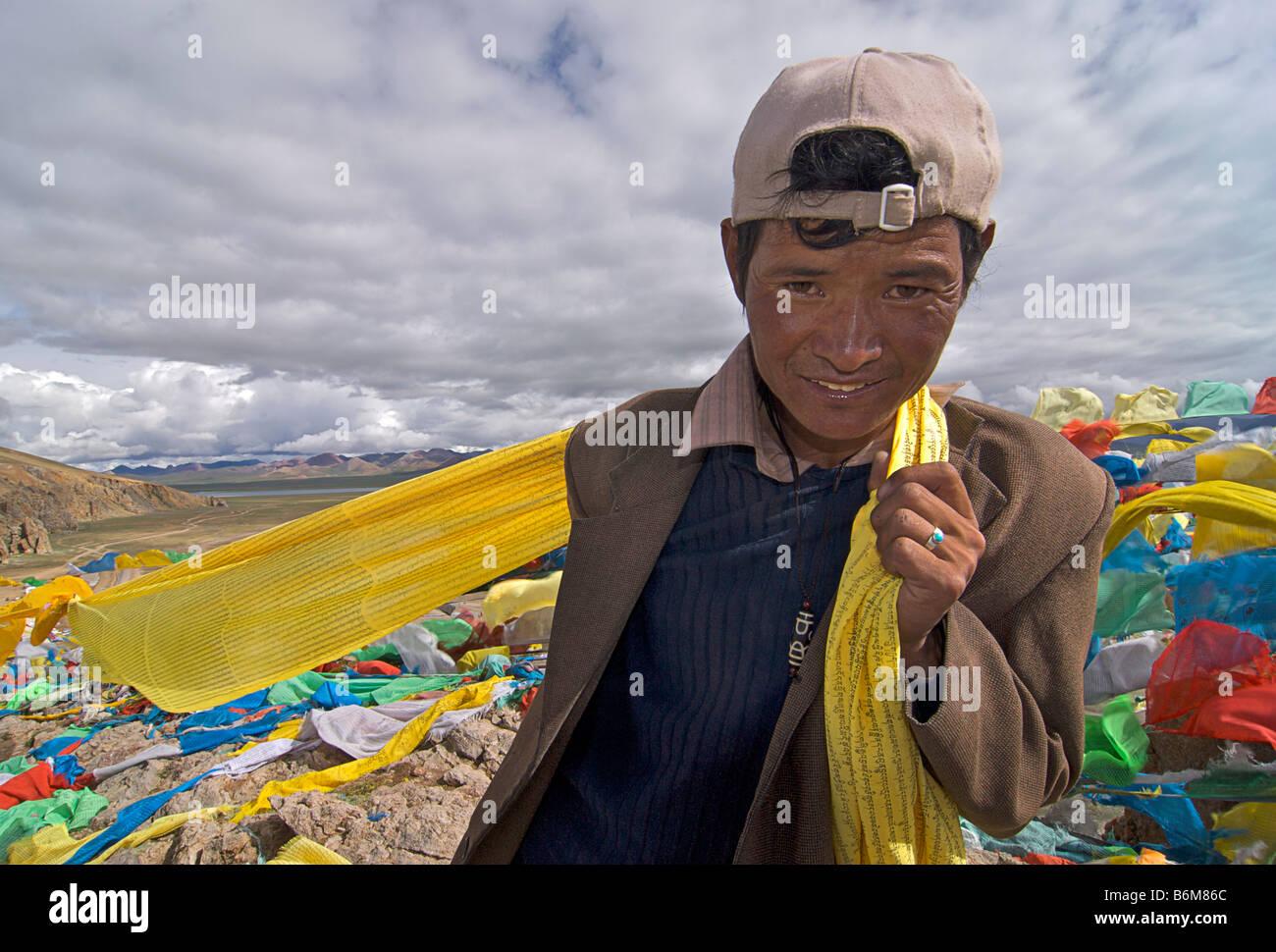 Tibetan man collecting loose prayerflags, Nam Tso Lake, Tibet - Stock Image