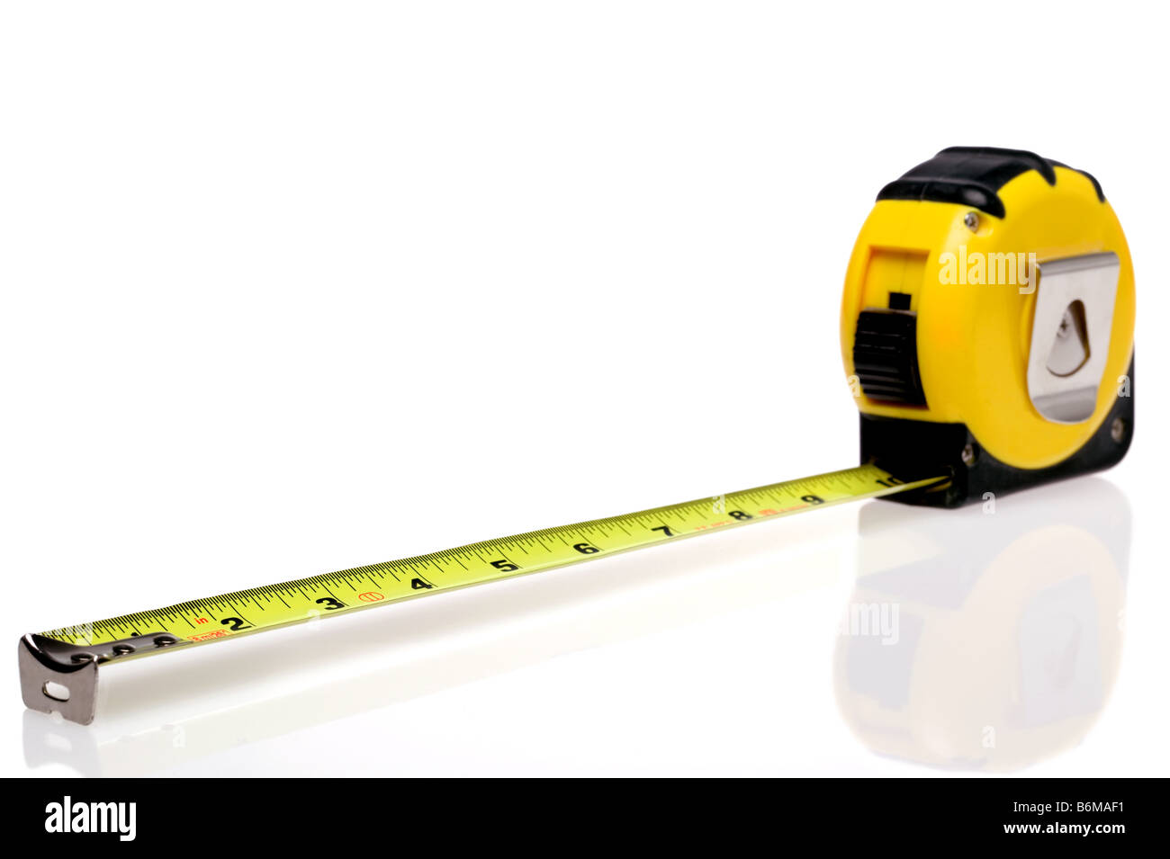 A yellow retractable steel tape measure isolated on a white background with slight reflection - Stock Image