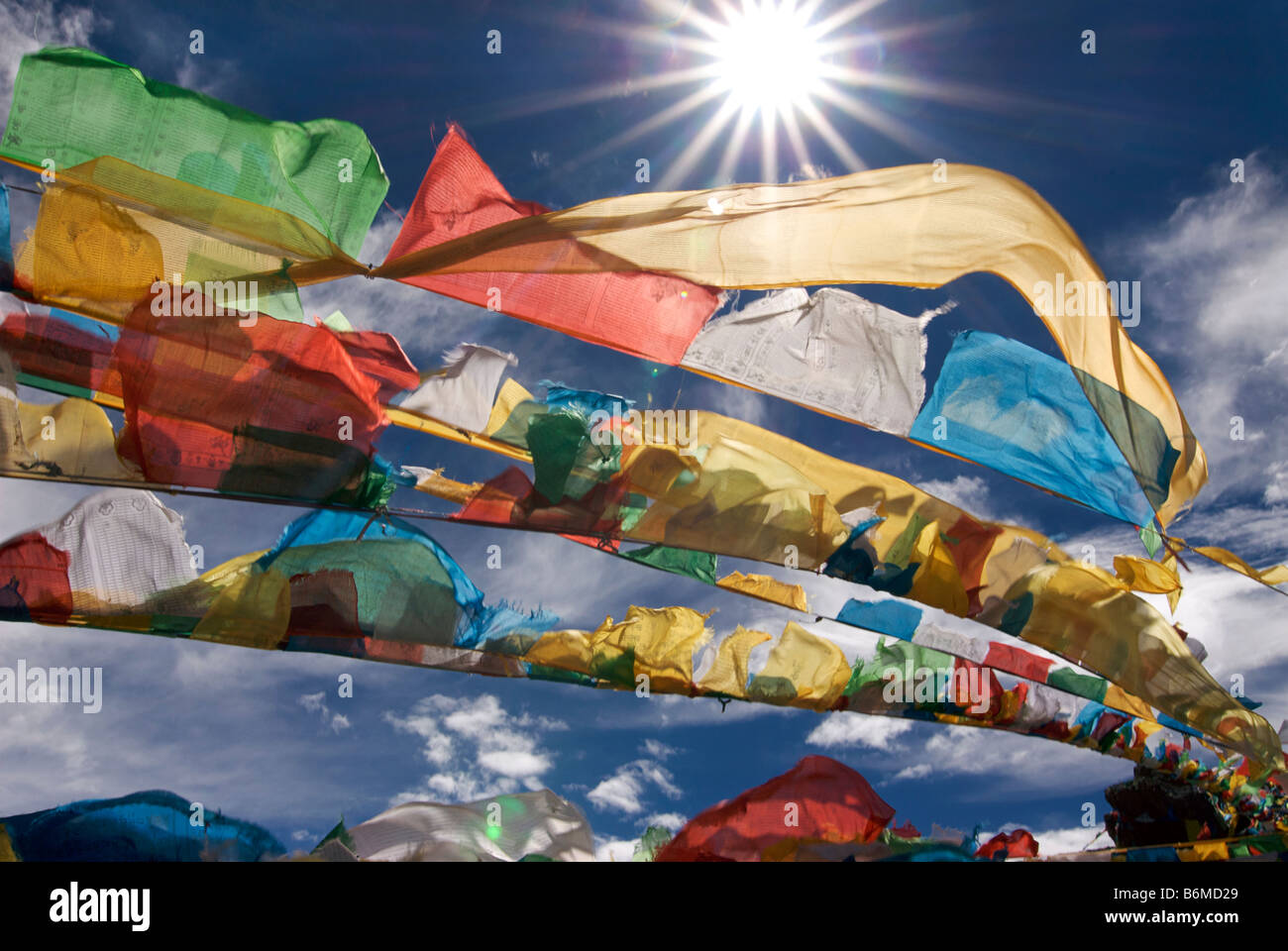 Prayer flags flapping in the midday sun atop an outcrop at Namtso lake, Tibet - Stock Image