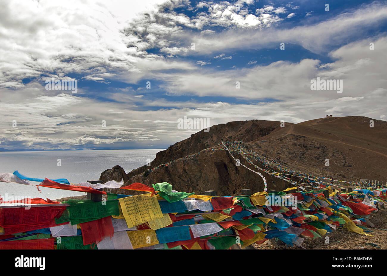 Prayerflags on a hilltop overlooking the sacred Tibetan lake at Nam Tso. Tibet - Stock Image