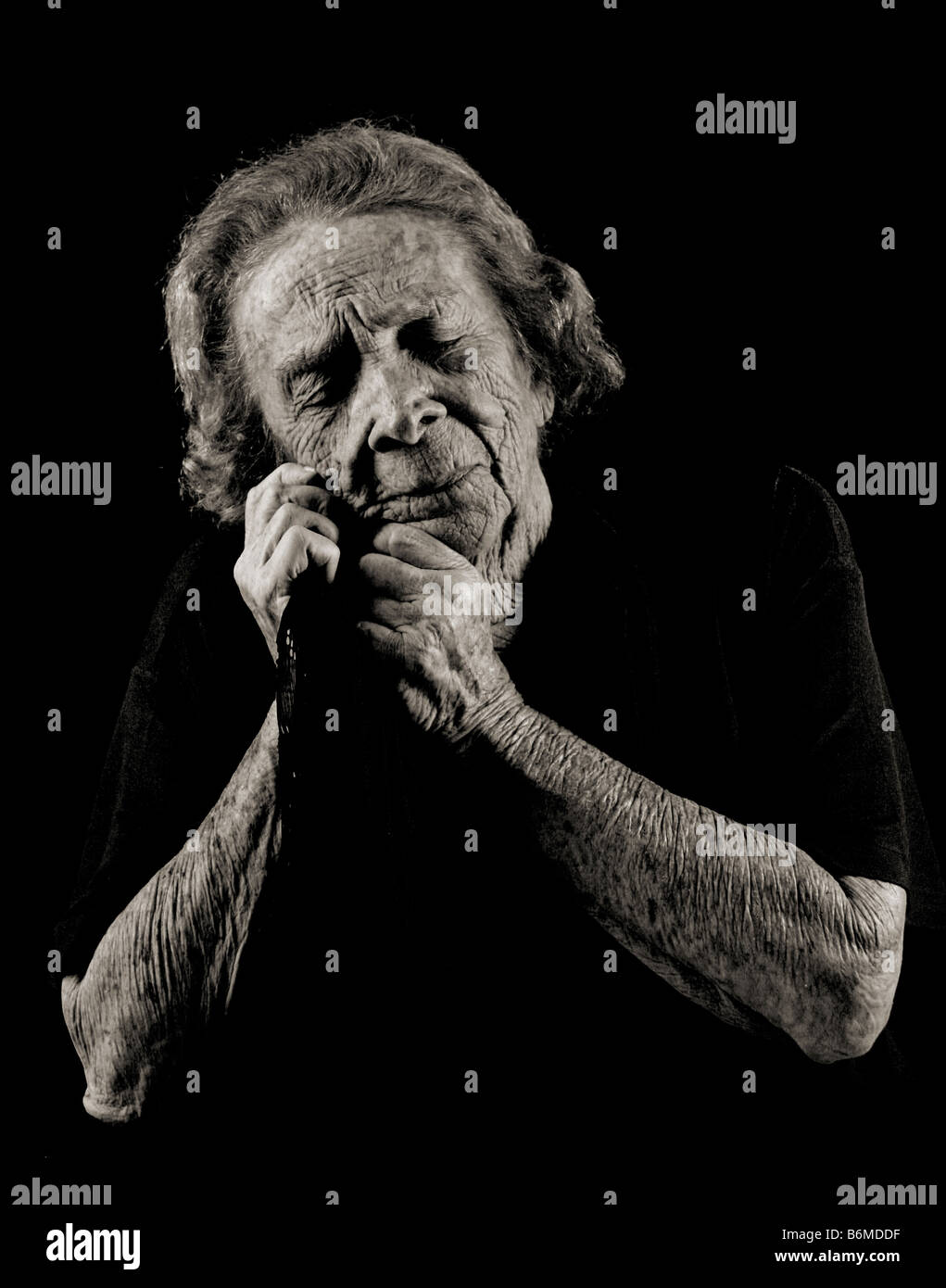 Black and White Portrait of an Elderly Woman Expressing Sadness While Reminiscing - Stock Image