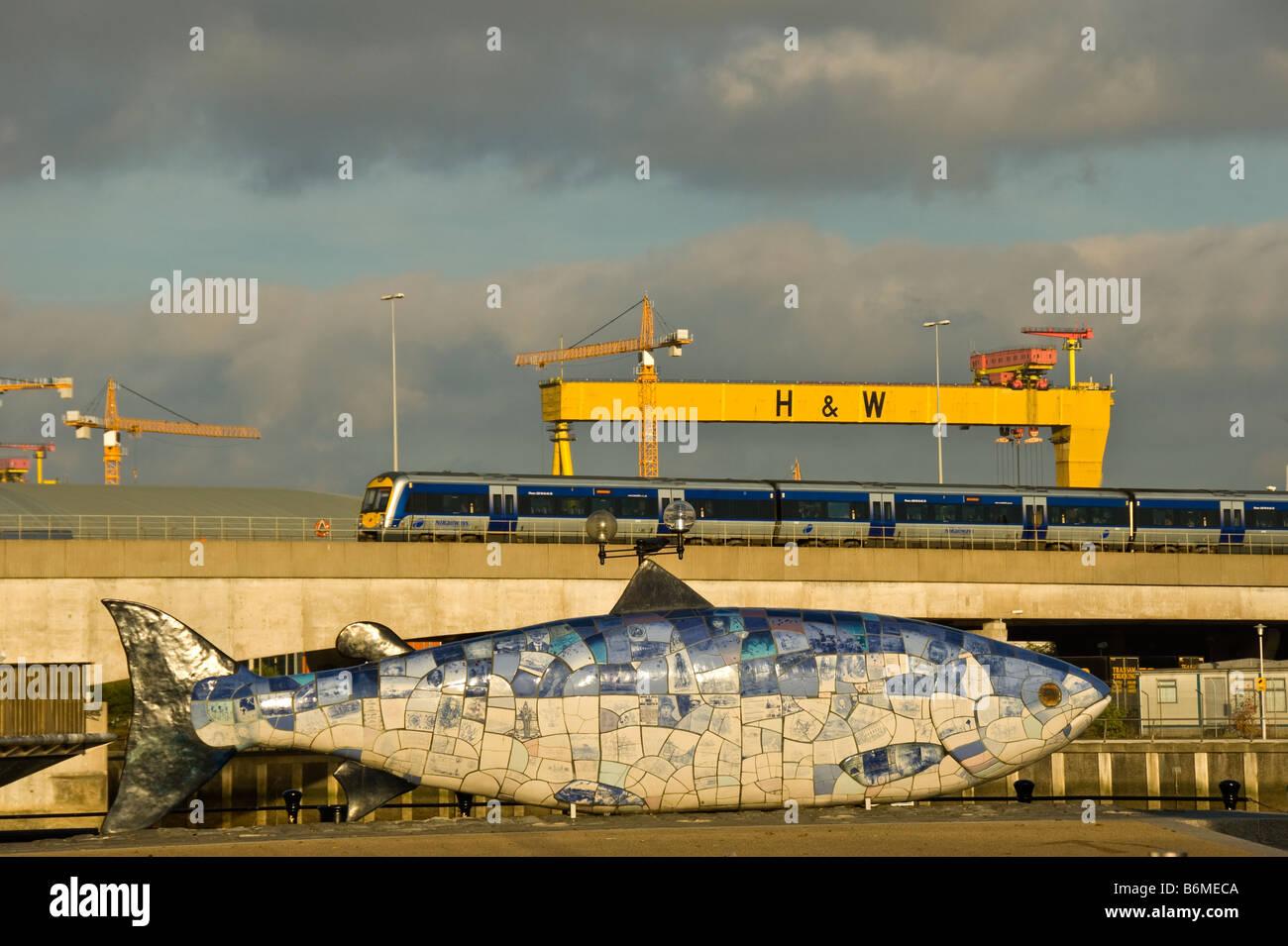 Belfast skyline big fish sculpture public art popular tourist attraction Northern Ireland HW yellow crane NI Railways - Stock Image