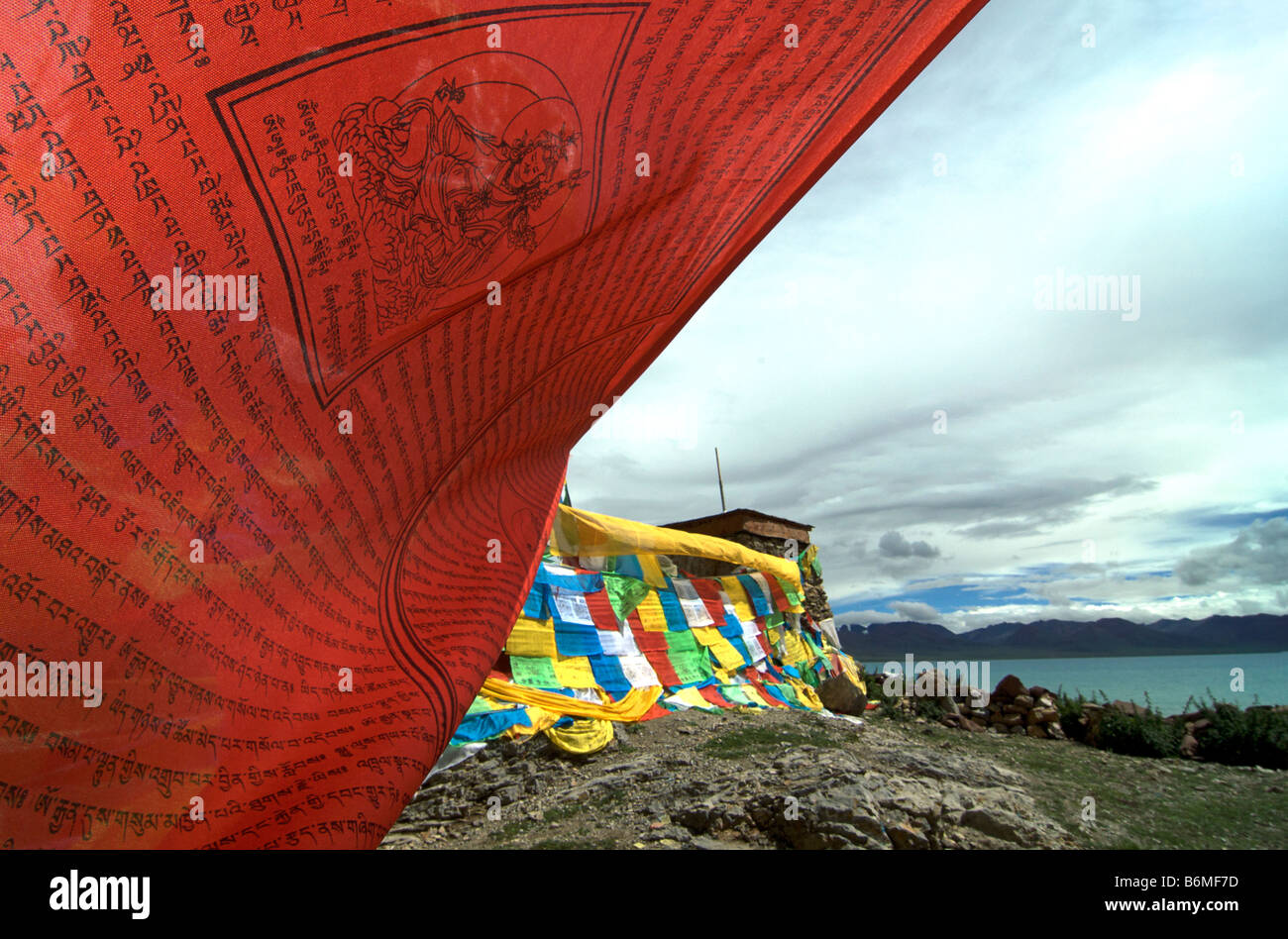 Red prayer flag flapping in the wind besides Namtso lake, Tibet - Stock Image