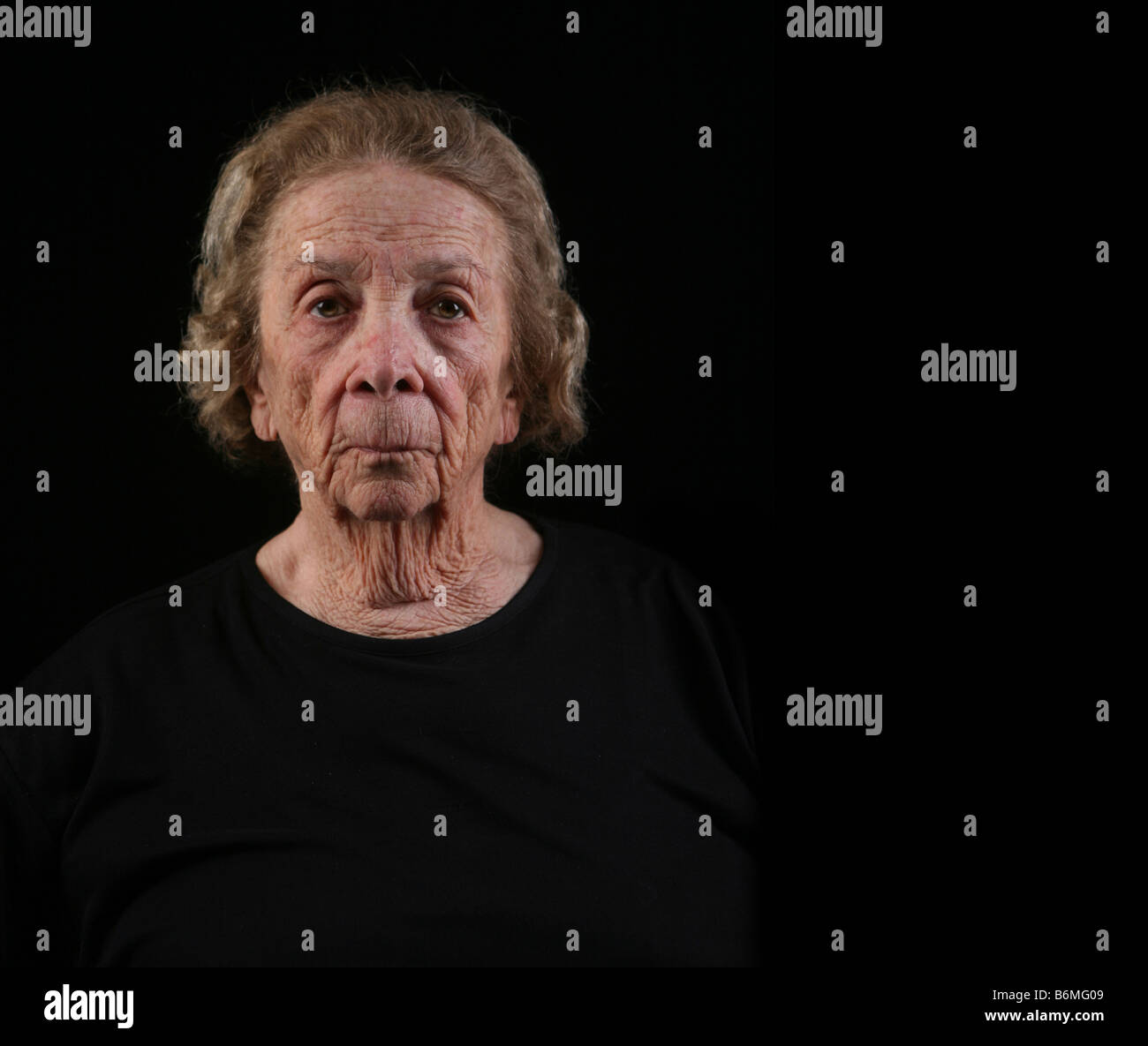 Senior Citizen Caucasian Woman in Deep Thought on Black Background - Stock Image